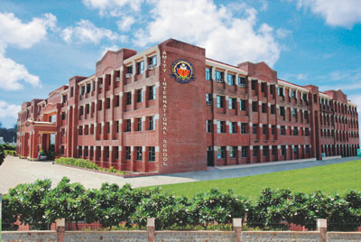 Schools in Gurgaon: Amity International School (Sector 46) - View of the school buildings with the logo clearly visible, and the lawns outside.